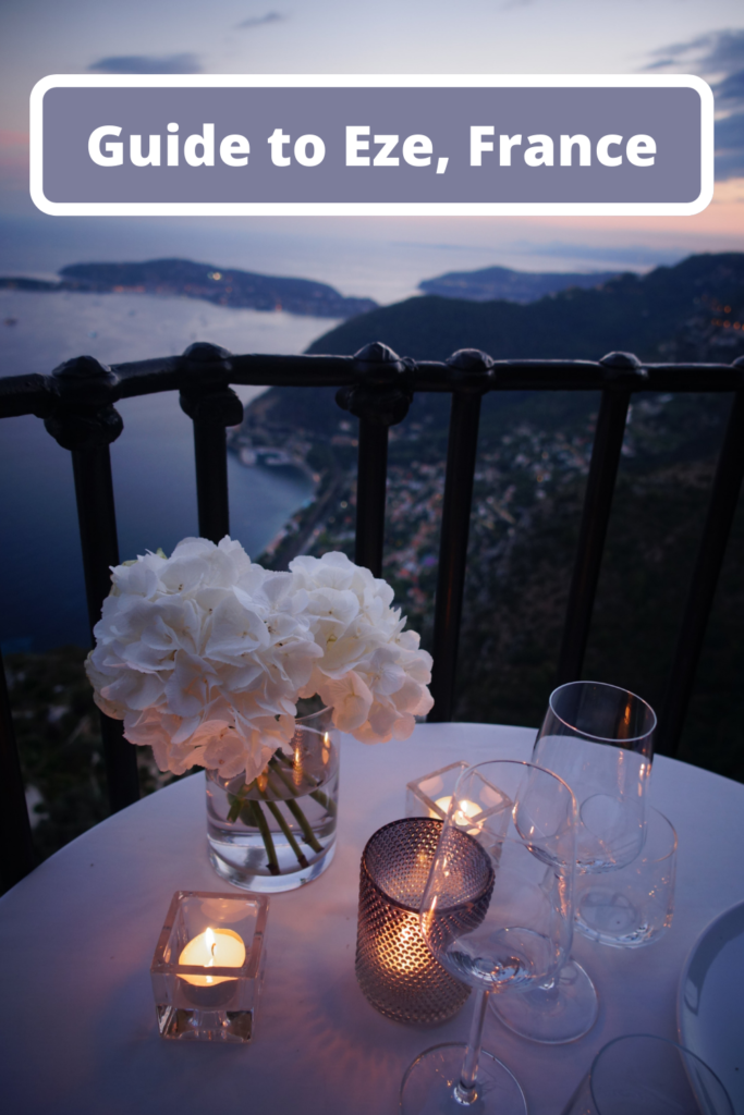 Dinner table with flowers and candle overlooking the sea in Eze, France at sunset